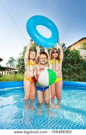 Full-length portrait of three happy kids playing with wind ball and swim ring in big inflatable pool outside