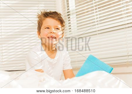Portrait of thoughtful kid boy sitting in his bed with a blanked book in sunny morning