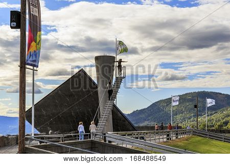 LILLEHAMMER, NORWAY - JULY 6, 2016: There are tourists near Olimpic torch that was built in 1993 specifically to the XVII Olympic Winter Games.