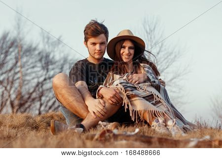 happy boho hipster couple hugging and sitting at sunset in mountains wearing hat and poncho space for text travel together