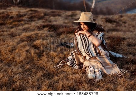 Happy Boho Woman Sitting At Sunset In Mountains, Wearing Hat And Poncho , Space For Text