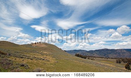 Rolling Hills under cirrus lenticular cloudscape in northern Yellowstone National Park in Wyoming US