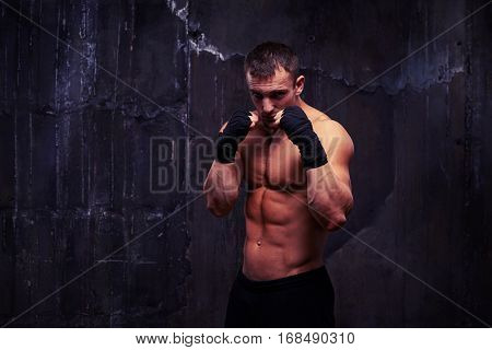 Mid shot of strong muscular bodybuilder who is standing in boxing pose against black wretched background. Handsome powerful athletic man strong bodybuilder with perfect biceps, triceps and chest
