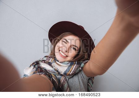 Portrait of a laughing woman in hat and scarf making selfie photo and winking over gray background