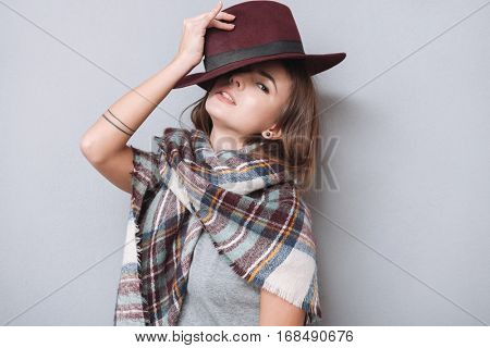Close up portrait of a charming young woman posing with hat and looking at camera isolated on the gray background