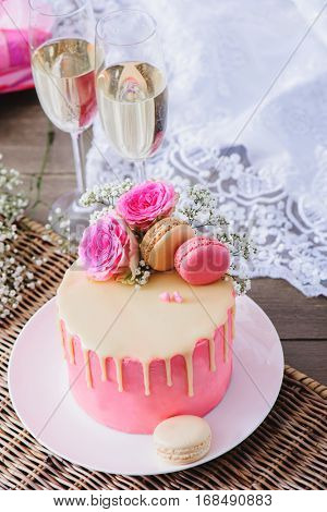 Pink romantic cake with champagne glasses standing beside
