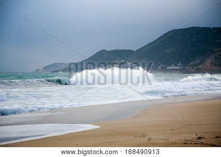 Seascape with with dramatic wave splash and turquoise water during storm on beautiful Cleopatra beach famous for it sand in Alanya Turkey in winter on gloomy day with Taurus Mountains as background.