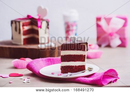 Slice of a red velvet cake and pink decoration around, present box in the background