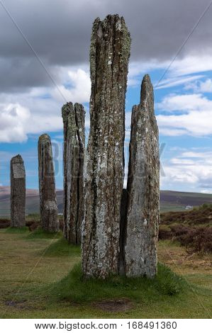 Orkneys Scotland - June 5 2012: Ring of Brodgar Neolithic Stone Circle. Multiple gray menhirs with white and yellow mold spots stand erect on a grass field under blue and gray sky. Hills in the background.