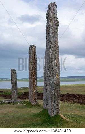Orkneys Scotland - June 5 2012: Ring of Brodgar Neolithic Stone Circle. Three gray menhirs with white and yellow mold spots stand erect on a grass field under blue and gray sky. Hills and Loch of Harray in the background.