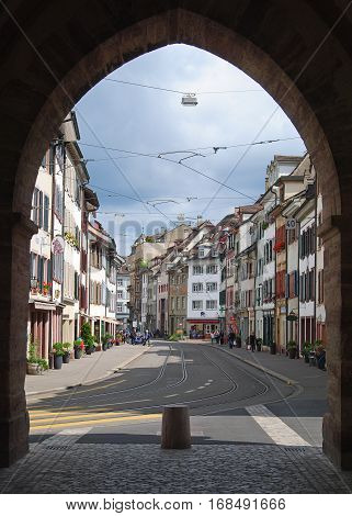 Basel, Switzerland - July 12, 2014. View of Spalenvorstadt street through the 600-year-old Spalentor city gate in Basel, with historic buildings, tram tracks, commercial properties and people.