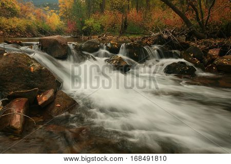 Rushing white water with fall color backdrop