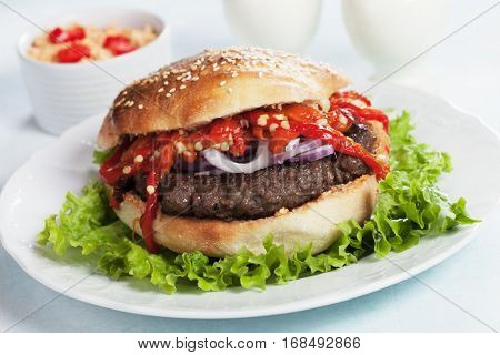 Pljeskavica, serbian style beef burger with onion and roasted peppers