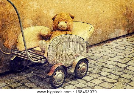 Old dirty Teddy bear toy sitting in the retro baby carriage on the street - lost lonely children concept, vintage hipster grunge image