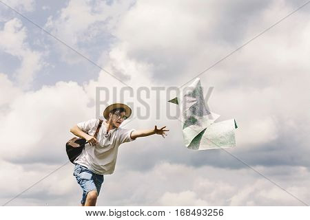 hipster traveler on top of mountains with amazing sky clouds view and catching his map funny moment travel lost concept space for text