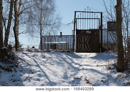 Belarus - The door to private ownership rusty iron door snowy path up clear weather a rickety wire fence.