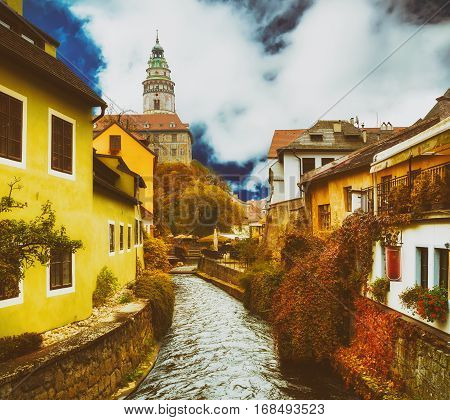 Cesky Krumlov - a famous czech historical beautiful town, view to the city river and beautiful autumn street with cjlorful buildings and chapel. Travel vintage hipster european background