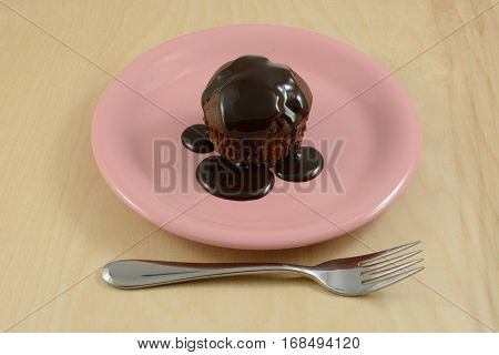 Chocolate cupcake with chocolate chips and chocolate syrup topping on pink dessert plate and fork