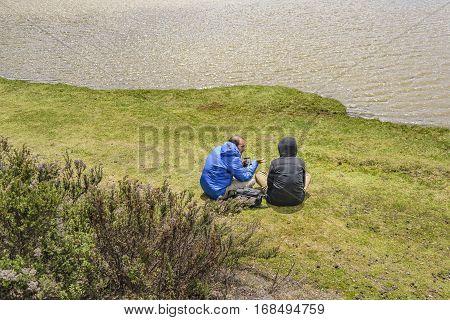 COTOPAXI, ECUADOR, FEBRUARY - 2016 - Couple talking at shore of lake in Cotopaxi national park Ecuador