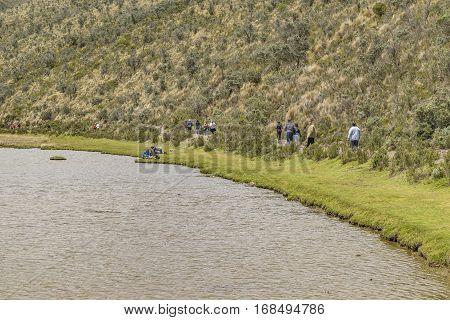 COTOPAXI, ECUADOR, FEBRUARY - 2016 - Group of people trekking a trail over lake at Cotopaxi national park Ecuador