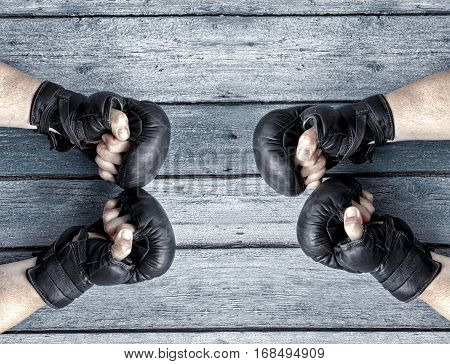 Two pairs of human hands in black leather boxing gloves facing each other a vintage wooden background