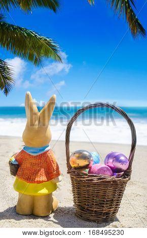 Easter bunny with basket and color eggs on the sandy beach near ocean