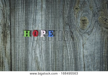 Words of hope from small multi-colored wooden letters empty space on the right