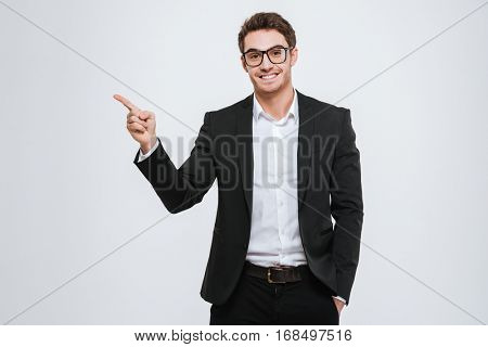 Portrait of a happy businessman in eyeglasses pointing finger away over white background