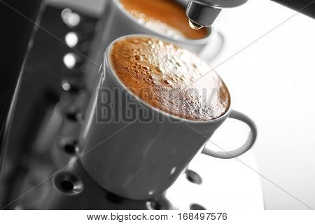 Two cups with fresh espresso in new coffee maker, closeup