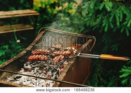 Delicious Grilled Sausages Roasting On Grates With Flames And Smoke, Bbq Outdoors At Summer Picnic,