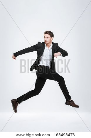 Full length business man in black suit jumping in studio isolated on a white background