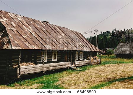 Old Wooden House Cabin With Hay In Country Side In Ukraine In Sunny Summer Mountains