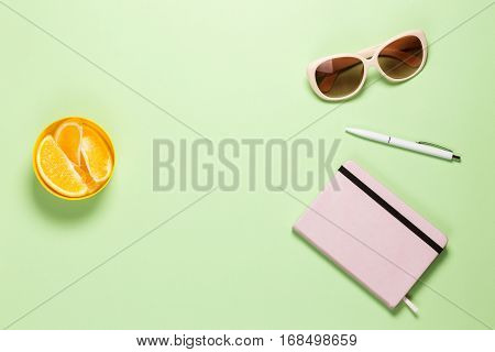 Modern Feminine Freelancer Workspace. Flat Lay Pistache Table with Rose Diary, White pen, Creamy Eyeglasses, Oranges in Cup. Copy Space, Top View. poster