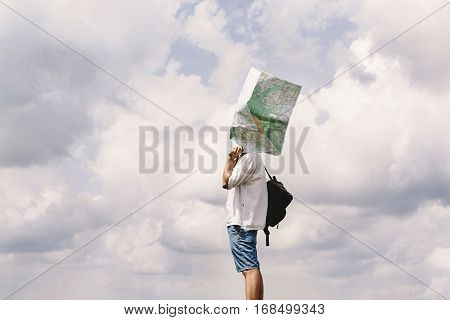 Hipster Traveler On Top Of Mountains With Amazing Sky Clouds View And Map At His Head, Funny Moment,