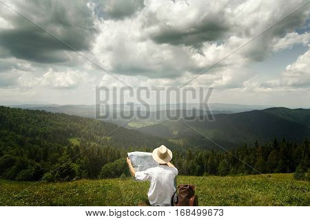 Man Traveler Exploring Map And Sitting On Top Of Sunny Hill On Background Of Amazing View On Mountai