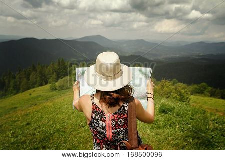 Woman Traveler Holding Map And Looking At It Exploring On Top Of Mountains, Travel Or Navigation Dir