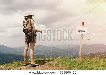 Stylish Hipster Woman Traveler With Backpack Holding Map And Exploring On Top Of Mountains, Travel