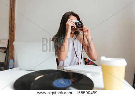 Image of casual young woman working on a laptop sitting on the chair in the house while using camera.