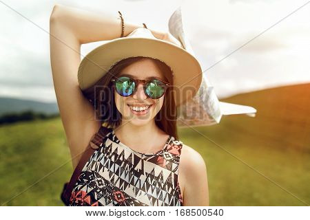 Stylish Hipster Woman Traveler Holding Map, With Fashionable Sunglasses And Hat Smiling On Top Of Mo