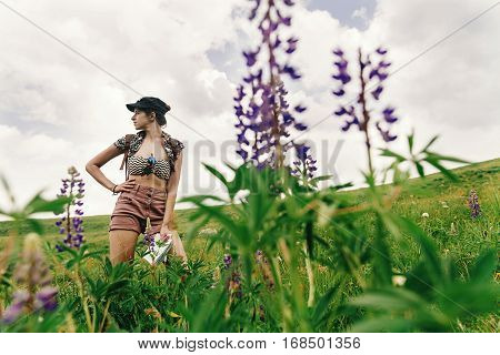 Stylish Hipster Woman Traveler Standing Among Wildflowers And  Lupin In Mountains, Travel And Summer