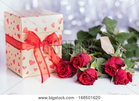 Cute gift box with hearts ornament and a bunch of flowers. Horizontal studio shot.