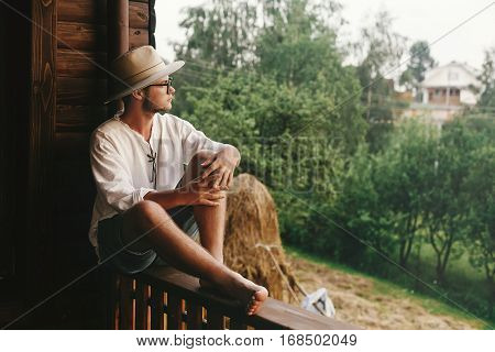 Hipster Man Sitting On Porch Of Wooden House  With Field And Hay In Evening, Calm Moment, Summer Far