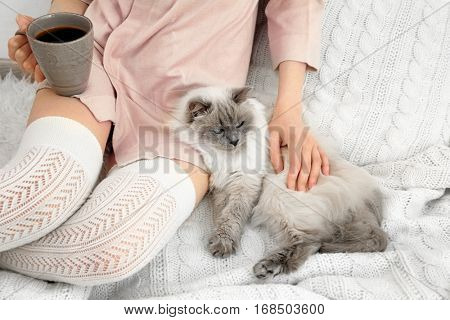 Young woman with cute funny cat resting at home