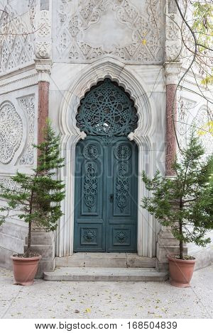 Detail of an ornate Victorian brick archway and wooden door of a church.