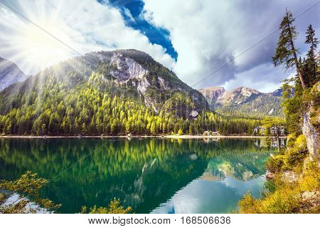 The concept of walking and eco-tourism. Water reflects mountains and forest.  Magnificent lake in South Tyrol. Sunshine on autumn day