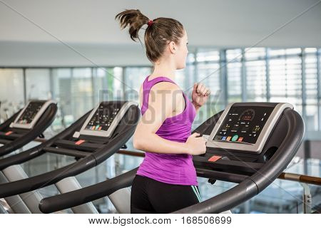 Fit woman running on treadmill in the gym