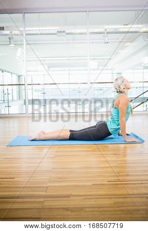 Fit blonde doing yoga on mat in the studio