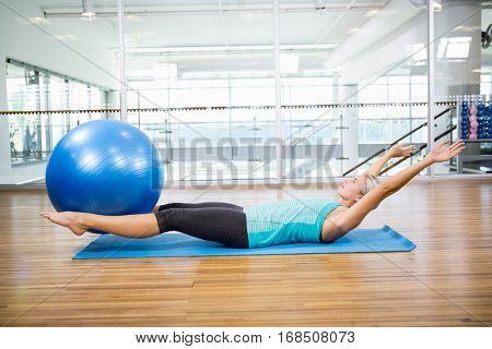 Fit blonde on mat holding fitness ball with legs in the studio