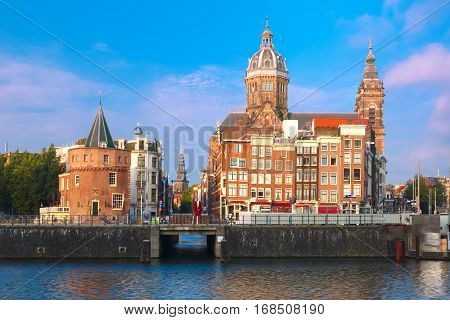 Amsterdam canal and Basilica of Saint Nicholas, Schreierstoren or Weepers Tower and Oude Kerk in the morning, Holland, Netherlands.
