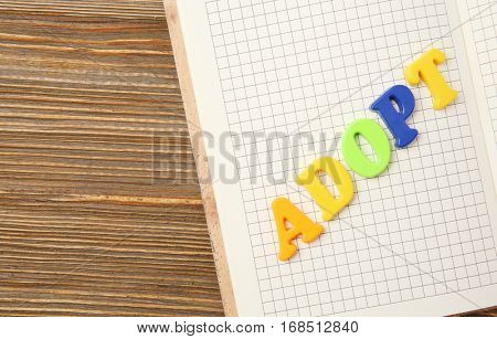 Word ADOPT and open notepad on wooden background, closeup